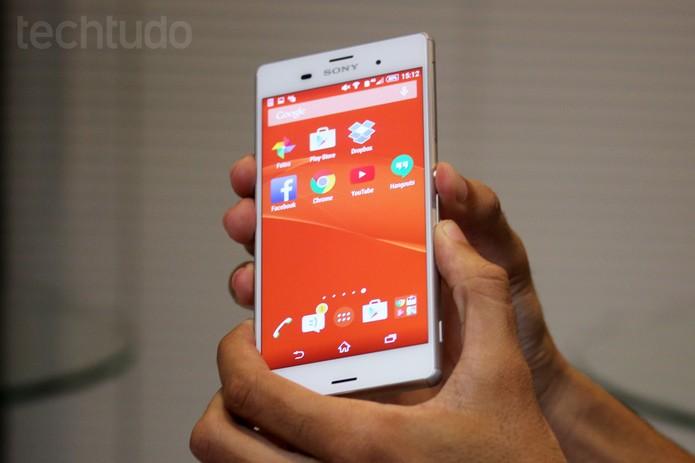Botões de liga e desliga e de volume do smartphone Sony Xperia Z3 sendo pressionados com as duas mãos (Foto: Nicolly Vimercate/TechTudo)
