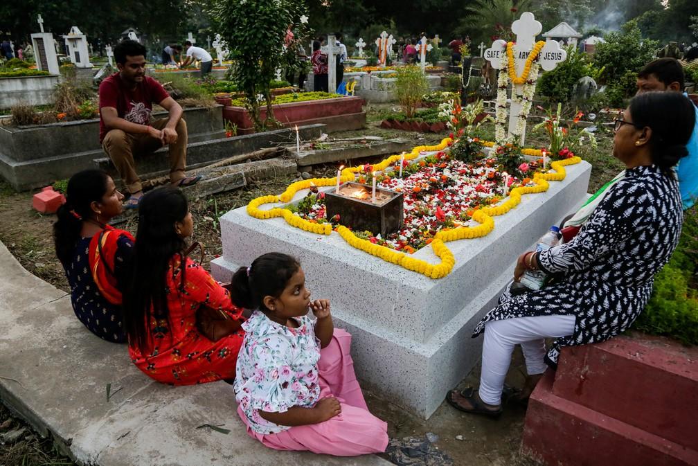 Uma família se reúne para rezar ao redor de um túmulo durante o dia de finados em Calcuta, na Índia, neste sábado (02) — Foto: Bikas Das/AP