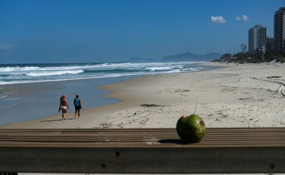 Foto mostra um coco na praia da Barra da Tijuca enquanto duas pessoas caminham na areia no Rio de Janeiro em meio à pandemia de Covid-19, a doença causada pelo novo coronavírus, no dia 27 de maio. — Foto: Ricardo Moraes/Reuters