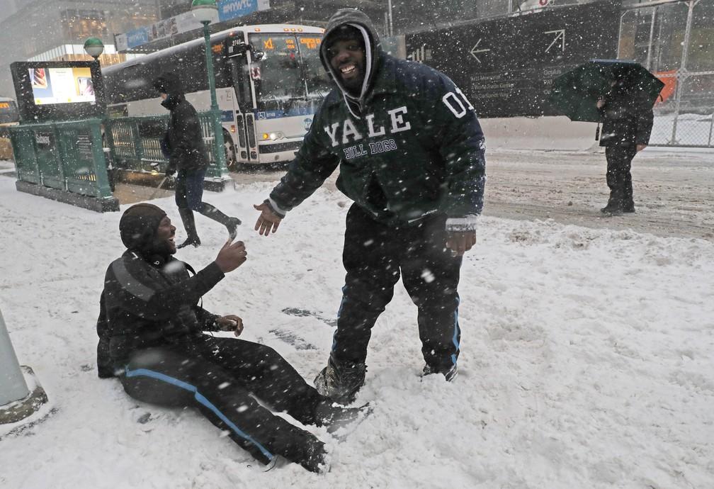Amigos dão risadas após um dele escorregar na neve ao atravessar uma rua em lower Manhattan, Nova York (Foto: AP Photo/Kathy Willens)