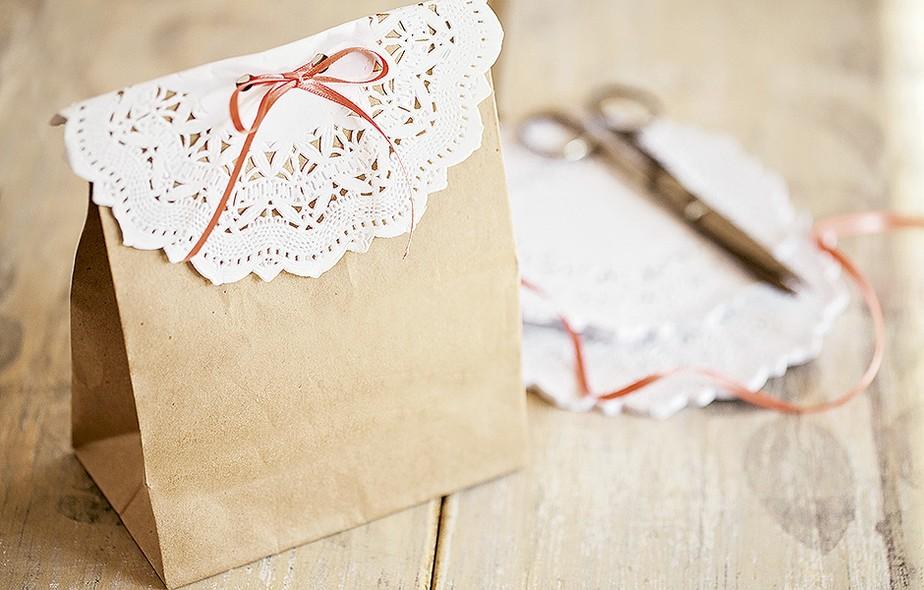 O saquinho de papel pardo vira embrulho exclusivo com a ajuda de uma renda de papel e um laço