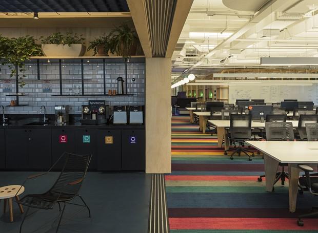 Azulejos de metrô cobrem a parede da cozinha industrial, que fica diretamente ligada mesa de trabalho conjunto. Ali, a paleta de cores vai do preto e branco para o carpete colorido (Foto: estudio guto requena | 2018)
