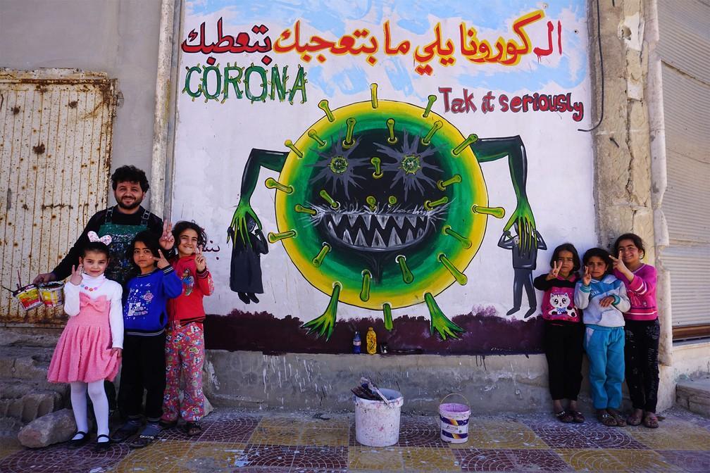 23 de março - O artista sírio Aziz al-Asmar posa com crianças diante de sua nova obra, que representa o agente da Covid-19 com as frases em árabe: 'O Corona do qual você não gosta lhe deixa doente' e 'Leve-o a sério', em um muro de Binnish, Idlib, no noroeste da Síria — Foto: Muhammad Haj Kadour/AFP