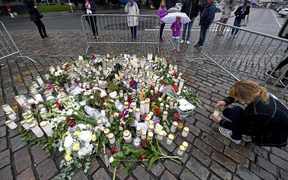 Mulher coloca vela em memorial na Praça do Mercado de Turku, em homenagens às vítimas de um homem que esfaqueou várias pessoas (Foto: Vesa Moilanen / Lehtikuva / via AFP Photo)