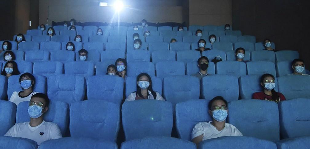 Público usa máscara e respeita distanciamento enquanto assiste a filme em um cinema recém-reaberto em Hangzhou, na província de Zhejiang, no leste da China, nesta segunda-feira (20) — Foto: Chinatopix via AP
