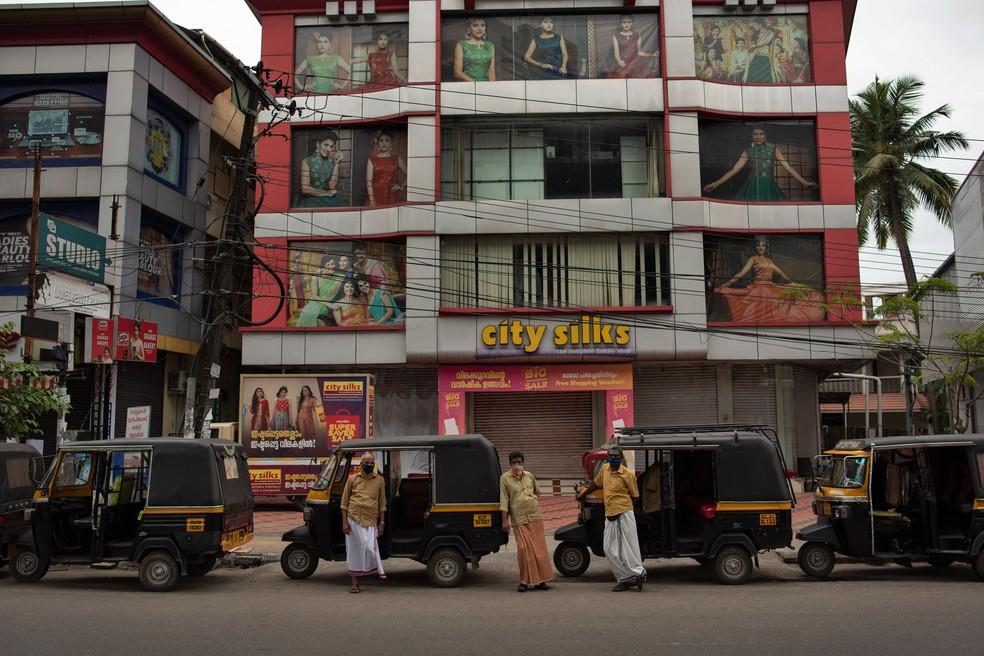 Motoristas de riquixá esperam por clientes fora de uma loja de roupas fechada em medida de contenção na propagação do novo coronavírus em Kochi, estado de Kerala, na Índia, neste sábado (18)  — Foto: R S Iyer/AP