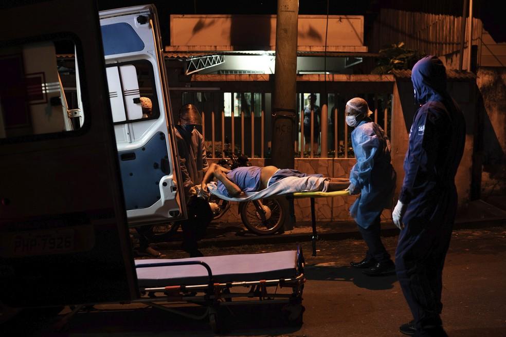 2 de junho - Trabalhadores de serviços de emergência transportam paciente idoso para  ambulância, em meio ao surto de coronavírus (COVID-19), em Manacapuru, Amazonas — Foto: Felipe Dana/AP