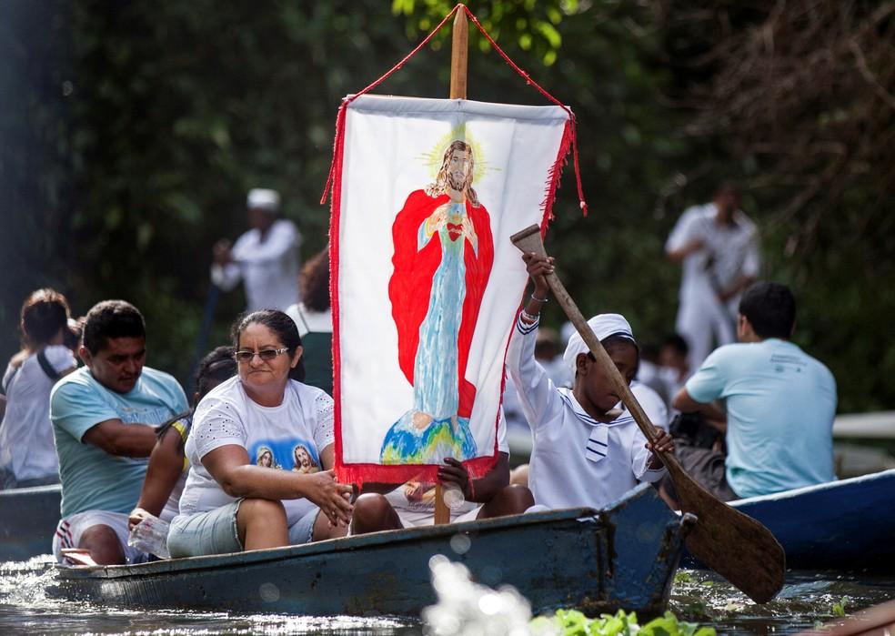 Peregrinos católicos exibem faixa com uma imagem de Jesus durante uma viagem de barco em Santa Izabel do Pará, no Pará, em 2012. — Foto: Paulo Santos/Arquivo/Reuters