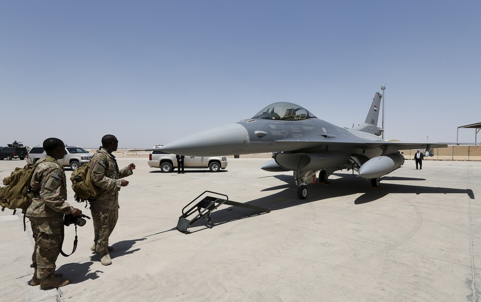 Militares norte-americanos obsevam jato F-16 na base em Balad — Foto: Reuters