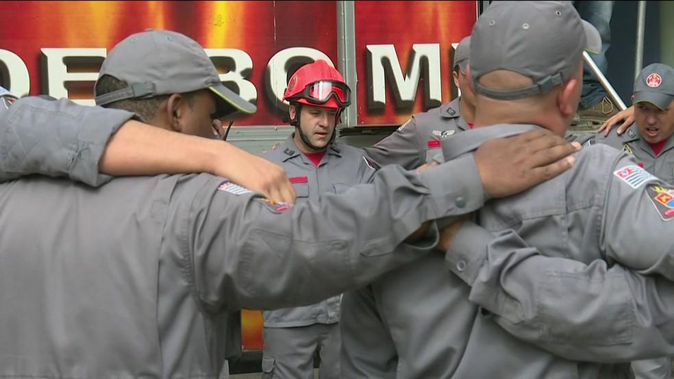 bombeiros que trabalharam nas buscas do prédio que desabou no Centro de SP se abraçam para fazer oração (Foto: Reprodução TV Globo)
