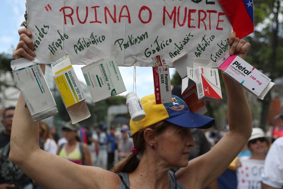 Opositora de Nicolás Maduro de Caracas segura cartaz com a mensagem 'ruína ou morte' em crítica contra a falta de medicamentos na Venezuela — Foto: Martin Mejia / AP Photo