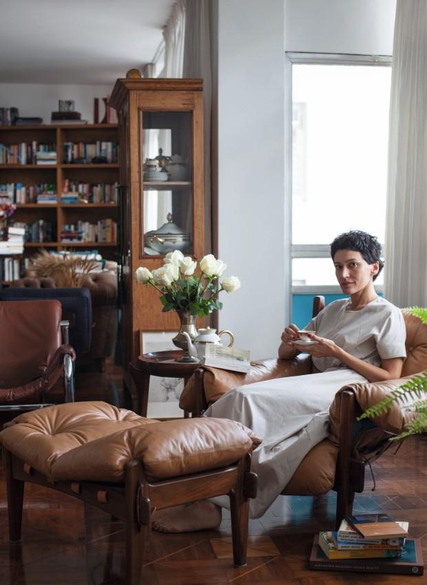 Dedé faz uma pausa para o café, curtindo o jogo de porcelana que foi de seu avô. O vaso ao fundo também é uma herança de família. A poltrona Mole, de Sergio Rodrigues, é da Loja Teo (Foto: Mayra Azzi / Editora Globo)