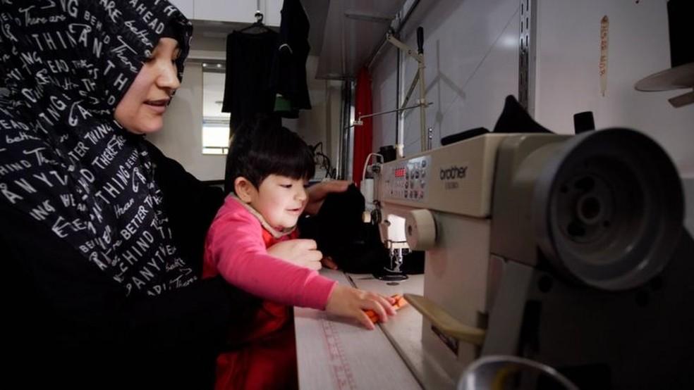 Kalbinur, fotografada com seu filho Merziye, costura roupas para sustentar sua família — Foto: BBC