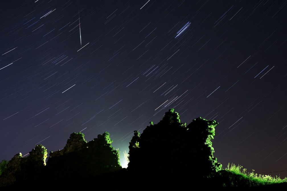 Foto tirada com longa exposição mostra um meteoro Perseid cruzando o céu na vertical e o rastro das estrelas acima das ruínas de um castelo medieval na vila de Kreva, a cerca de 100 km a noroeste de Minsk, na Bielorrússia  — Foto: Sergei Gapon/AFP