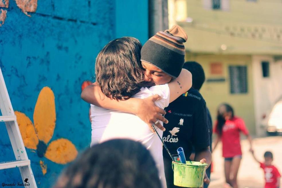 Morador da comunidade Tubulação, em Itaquaquecetuba, abraça voluntário que ajudou a colorir vielas (Foto: Andressa Silva/Gerando Falcões)