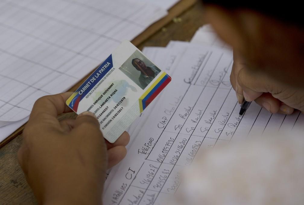 Carnê da pátria é necessário para ter acesso aos programas sociais do governo de Nicolas Maduro (Foto: Fernando Llano/AP)