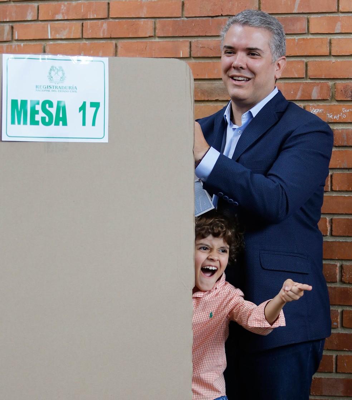 O candidato à Presidência da Colômbia Ivan Duque, do partido Centro Democrático, vota em uma urna em Bogotá enquanto seu filho rouba a cena fazendo caretas para a família e os fotógrafos na sala (Foto: Fernando Vergara/AP)