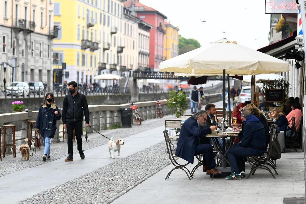 Pessoas almoçam ao ar livre em restaurante no canal Navigli, em Milão, no dia em que grande parte da Itália avança para a 'zona amarela' de restrições contra a Covid-19 nesta segunda (26) — Foto: Flavio Lo Scalzo/Reuters