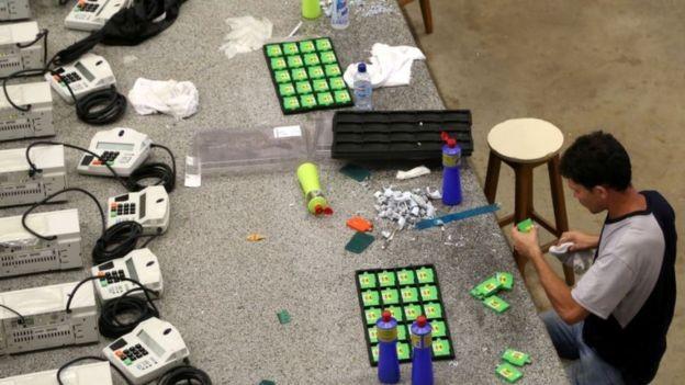 Urnas sendo preparadas por técnico em Cuiabá (MT) (Foto: TSE via BBC)