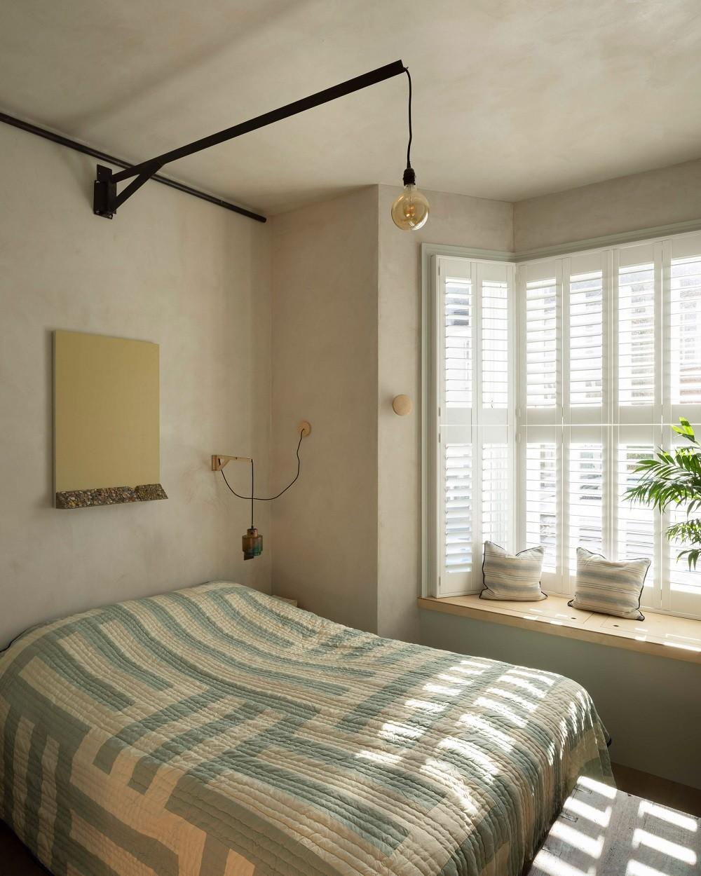 Uma luz de pivô de aço preto é responsável pela sutil iluminação artificial do quarto, assim como em outros ambientes da casa (Foto: Ståle Eriksen/Reprodução)