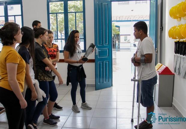 Alunas entregam a prótese feita com impressão 3D ao jovem Daniel da Silva, que teve a perna direita amputada depois do acidente (Foto: Divulgação)