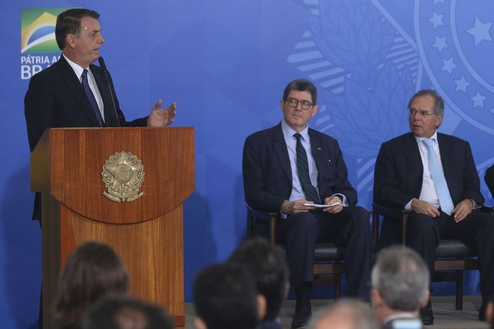 O presidente Jair Bolsonaro durante discurso no Palácio do Planalto diante do presidente do BNDES, Joaquim Levy, e do ministro da Economia, Paulo Guedes — Foto: Antonio Cruz/ Agência Brasil