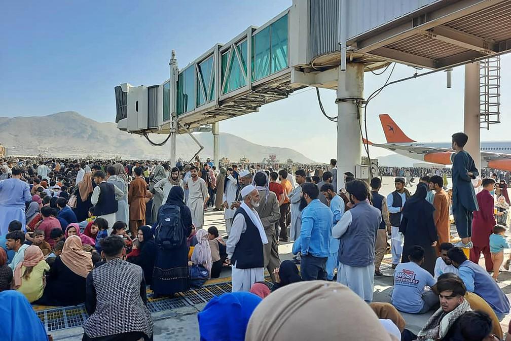 Afegãos se aglomeram na pista do aeroporto de Cabul no dia 16 de agosto para tentar fugir do país após o Talibã assumir o controle do Afeganistão — Foto: AFP