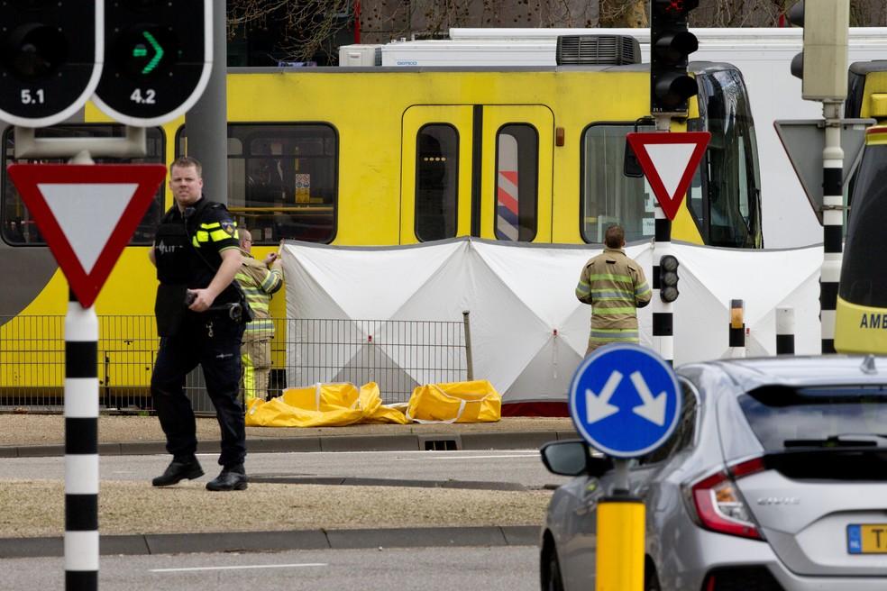 Equipe de resgate instala tela no local onde um corpo foi coberto com um cobertor branco após tiroteio em Utrecht, na Holanda, nesta segunda-feira (18) — Foto: Peter Dejong/AP