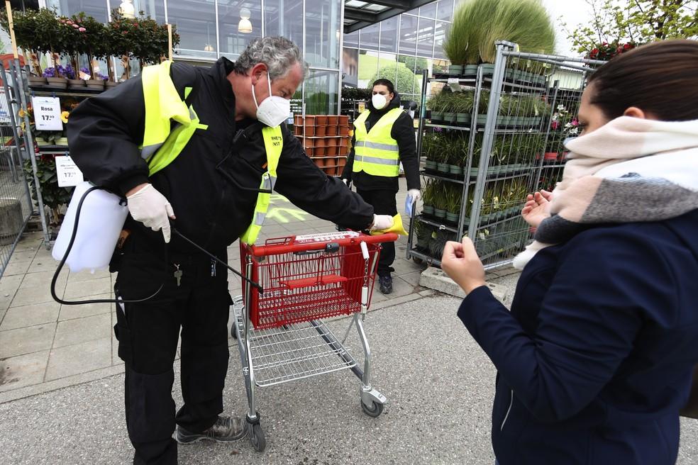 Um funcionário da segurança limpa carrinhos de compras na entrada de uma loja de jardinagem em Munique, na Alemanha, nesta segunda-feira (20) — Foto: Matthias Schrader/AP