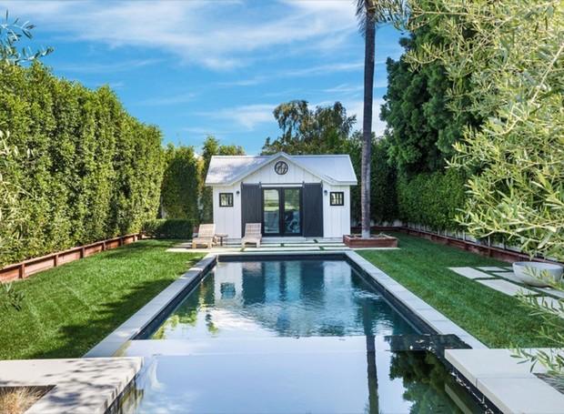 Uma edícula imita uma casinha pequena atrás da piscina (Foto: Variety/ Reprodução)