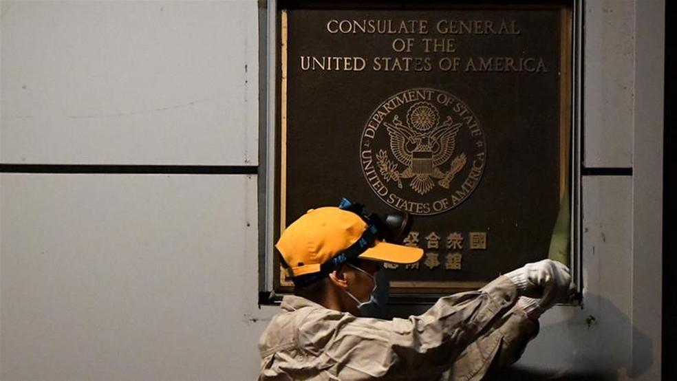 Funcionário retira placa que indica o funcionamento do consulado americano em Chengdu no domingo (26) — Foto: Thomas Peter/Reuters