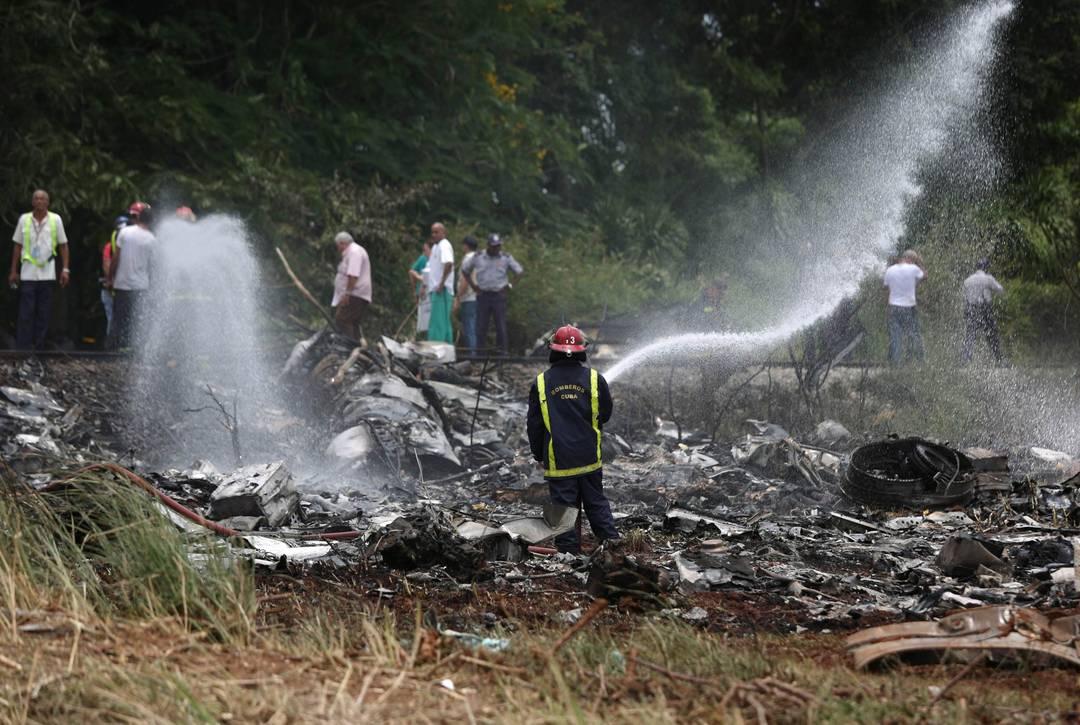 Bombeiro usa mangueira para aguar destroços após desastre aéreo em Havana, Cuba