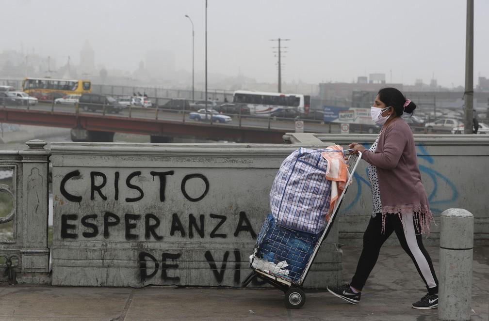 Uma vendedora ambulante passa por grafite com a mensagem em espanhol: 'Cristo, esperança para a vida' em Lima, no Peru, em julho de 2020 — Foto: Martin Mejia/AP
