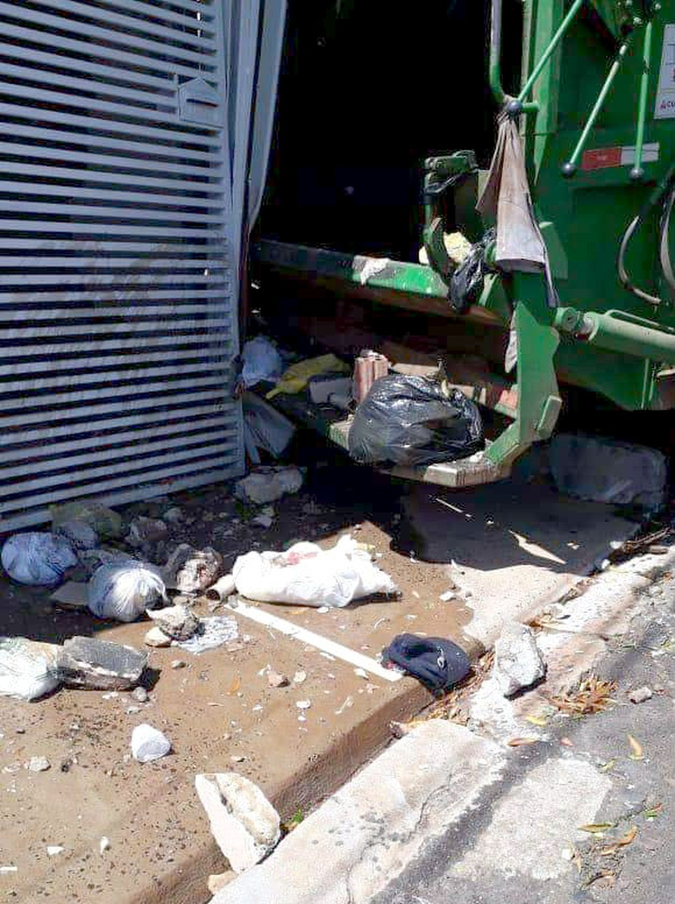 Na batida, lixo ficou espalhado na calçada e portão de ferro do imóvel acabou danificado — Foto: Arquivo pessoal