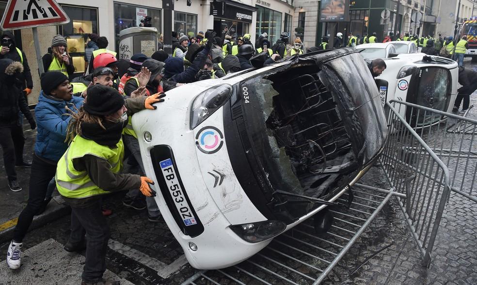 Manifestantes destroem carros durante um protesto em Paris, neste sábado (1º)  — Foto: Lucas Barioulet / AFP