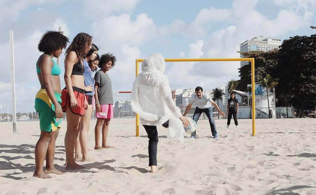 Na Praia de Cobacabana, Ziauddin Yousafzai defende uma bola chutada pela filha Malala, sob o olhar de garotas que participam do projeto Street Child United — Foto: Divulgação/Luisa Dörr para Malala Fund