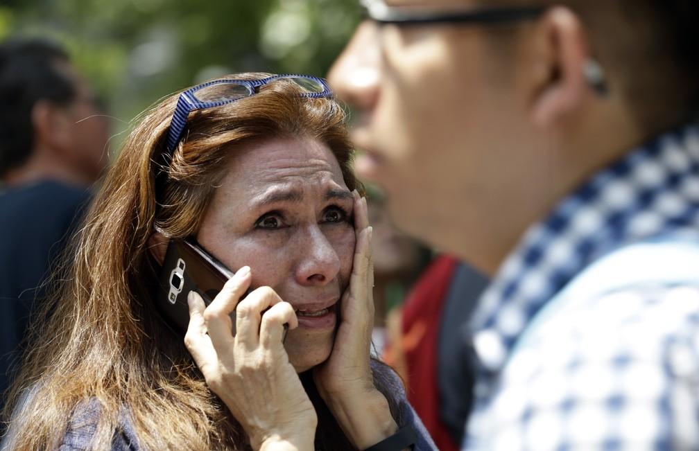 Mulher fala preocupada ao telefone em rua da Cidade do México após terremoto atingir a região  (Foto: Marco Ugarte/AP Photo)