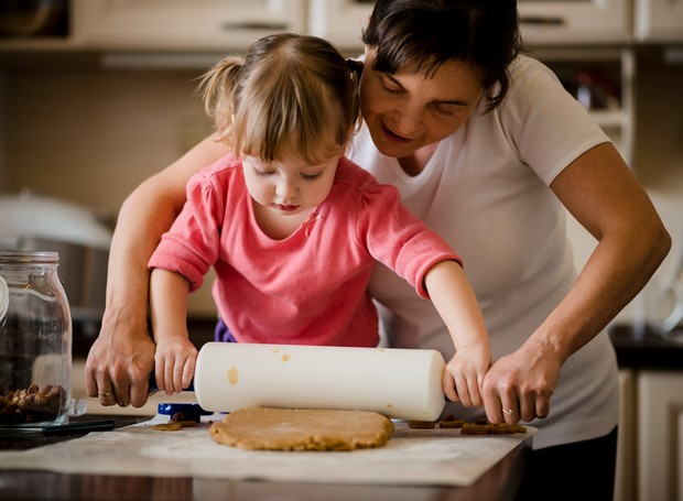 Mother and child preparing dough with rolling pin in kitchen at home (Foto: Getty Images/iStockphoto)