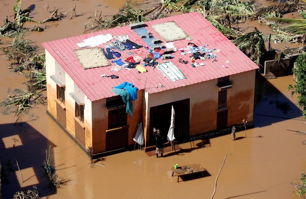 Homem acena perto da sua casa inundada após a passagem do Ciclone Idai no distrito de Buzi, perto de Beira, em Moçambique — Foto: Reuters/Siphiwe Sibeko