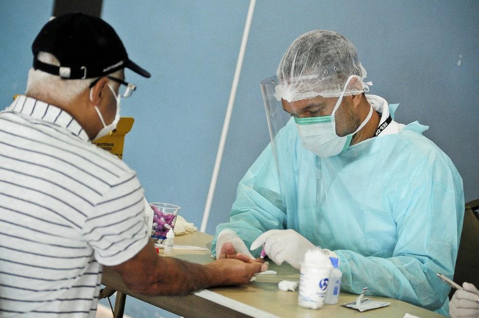 Profissional de saúde aplica exame sanguíneo em triagem de idosos no programa Hotelaria Solidária, no DF — Foto: Breno Esaki/Agência Saúde