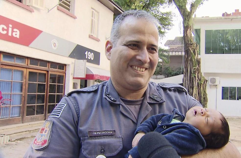PM segura bebê após salvá-lo em São Vicente (Foto: Reprodução/TV Tribuna)