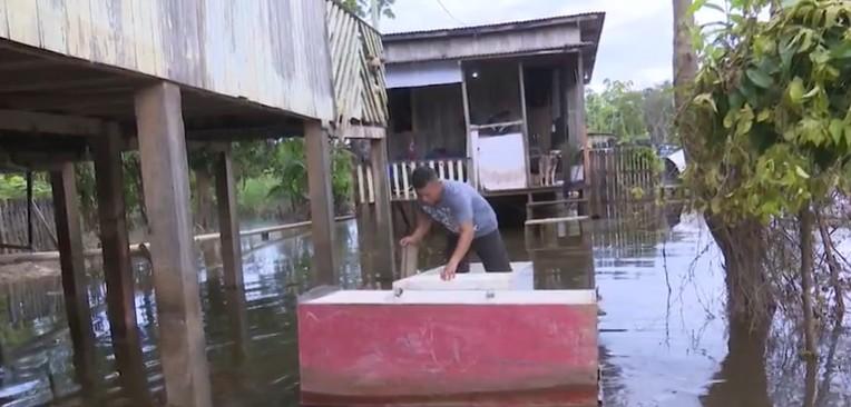 Sem ter como sair de casa, autônomo faz geladeiras de canoa em bairro atingido por cheia de rio em Rio Branco
