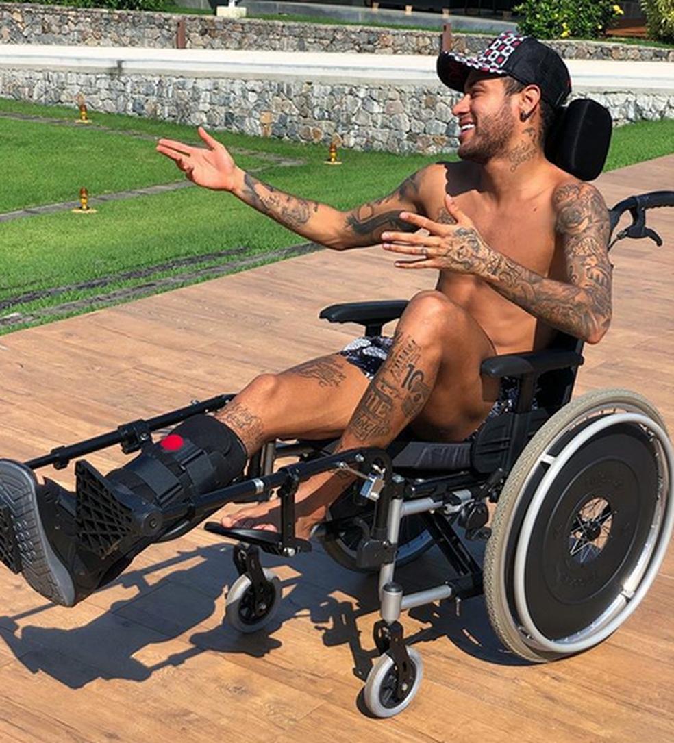 Neymar em cadeira de rodas durante recuperação no Brasil (Foto: Reprodução)