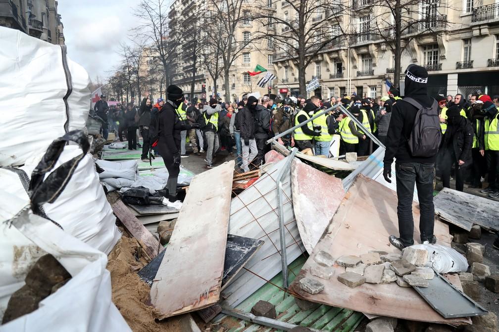 Coletes amarelos passam por barricada em Paris, durante protesto em Paris, neste sábado (9)  — Foto: Zakaria Abdelkafi / AFP