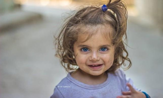 Menina síria posa para foto na cidade Homs, na Síria
