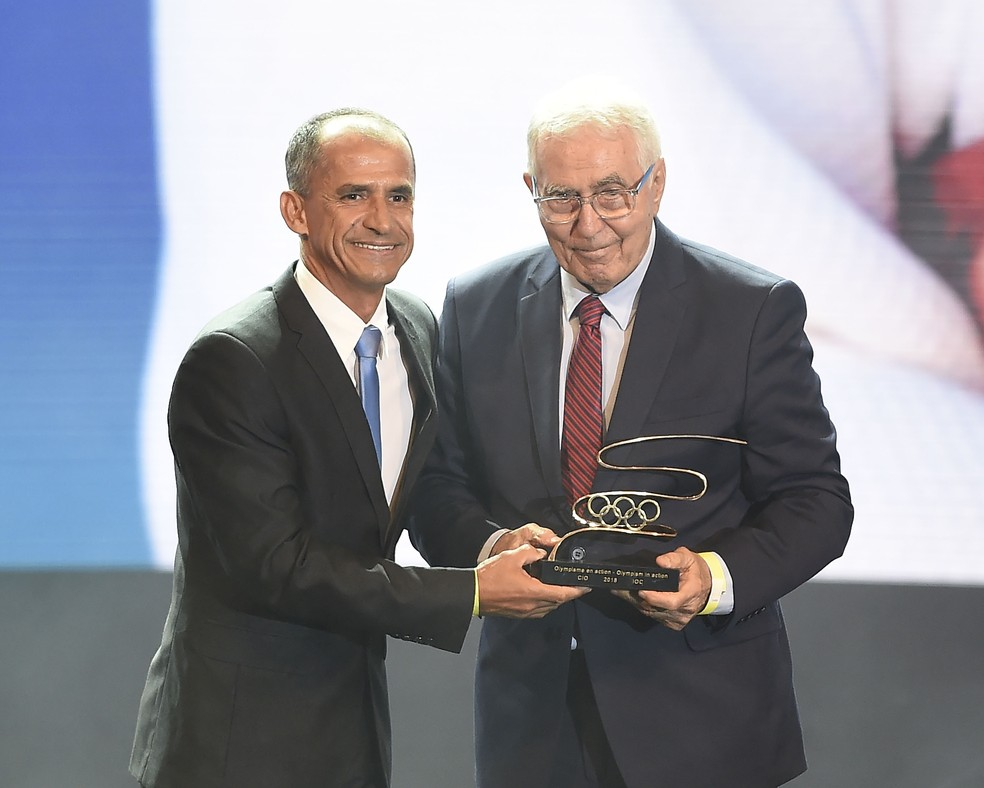 Geraldo Bernardes recebe o troféu das mãos de Vanderlei Cordeiro de Lima  — Foto: André Durão