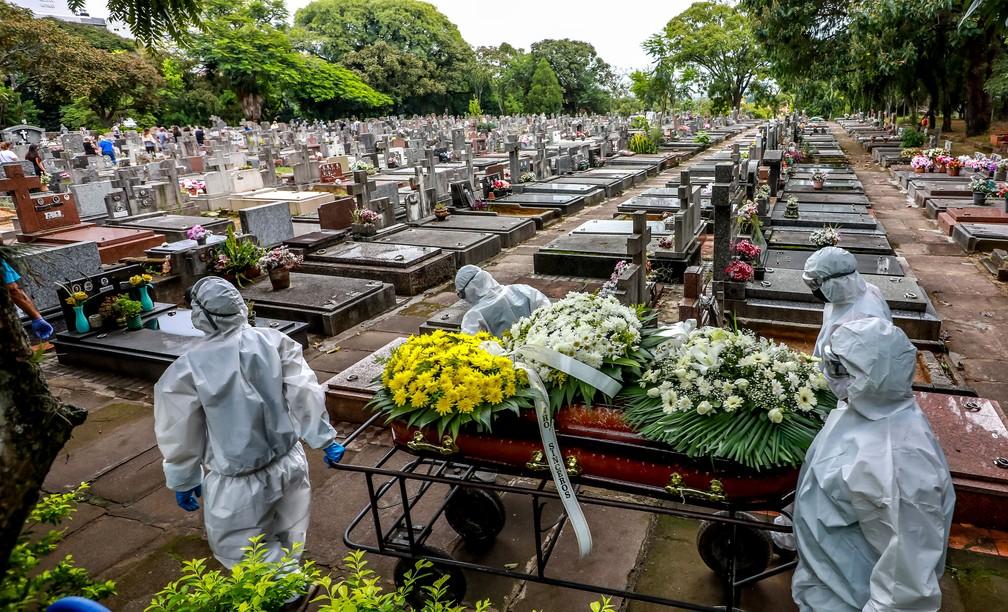Coveiros carregam caixão de vítima da Covid-19 em cemitério municipal de Porto Alegre na sexta-feira (26) — Foto: Silvio Avila/AFP