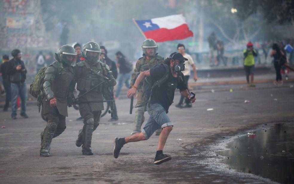 Manifestante foge de forças de segurança durante protesto em Santiago, no Chile, em 20 de dezembro — Foto: Reuters/Ricardo Moraes