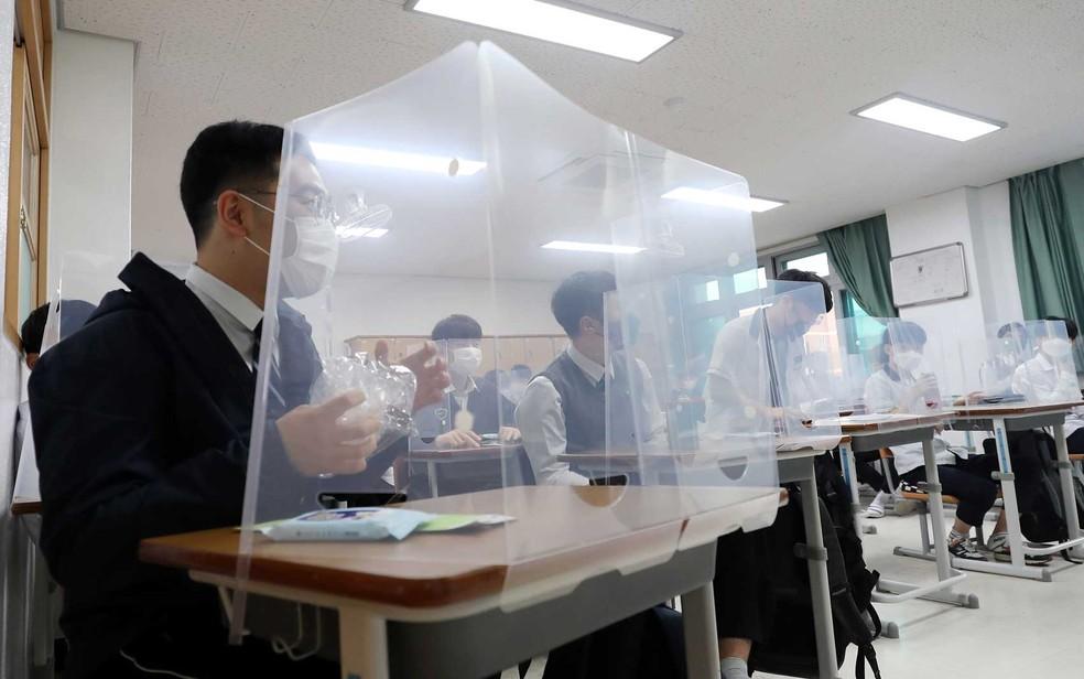 Alunos retomam aulas na Coreia do Sul; em algumas escolas, carteiras têm divisórias — Foto: Yonhap / AFP Photo