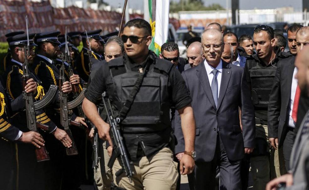 Premiê da Autoridade Palestina, Rami Hamdallah, é escoltado por guarda-costas ao ser recebido por forças do Hamas na chegada à Faixa Gaza, nesta terça-feira (13)  (Foto: Mahmud Hams / AFP)